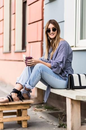 BERLIN, GERMANY - AUGUST 15: Fashion Blogger (She Comes In Colors) and Owner of SCIC Swimwear Sofia Grau (@shecomesincolors) drinking a Blueberry Smoothie wearing light blue denim jeans from H&M, a plaid Storets blouse, a black white H&M bag, round Ray Ban sunglasses and Miu Miu ballerinas shoes on August 15, 2016 in Berlin, Germany. (Photo by Christian Vierig/Getty Images) *** Local Caption *** Sofia Grau